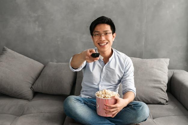 Retrato de un hombre asiático joven sonriente que sostiene las palomitas de maíz