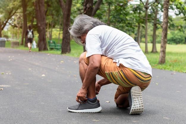 Retrato del hombre asiático mayor de los deportes que ata cordones de zapatos en el camino.