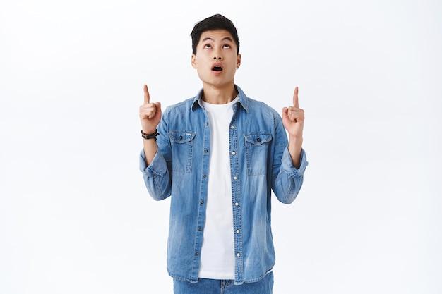 Retrato de hombre asiático sorprendido joven impresionado jadeando, boca abierta asombrado y mirando apuntando con el dedo hacia algo increíble, increíble oferta súper genial, pared blanca