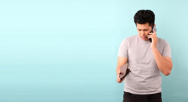 Retrato de hombre asiático sosteniendo un teléfono móvil conmocionado, sorprendido sin palabras. sosteniendo una billetera vacía en la pared azul.