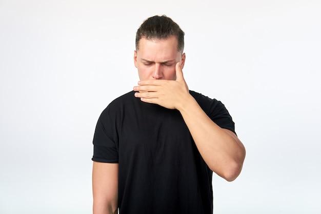 Retrato de hombre asustado cubriendo su boca con la mano. tiro del estudio