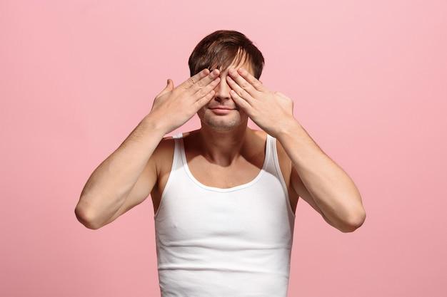 Retrato del hombre asustado en pared rosa