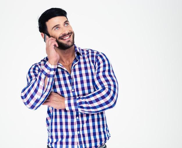 Retrato de un hombre atlético sonriente hablando por teléfono y mirando hacia arriba aislado en una pared blanca
