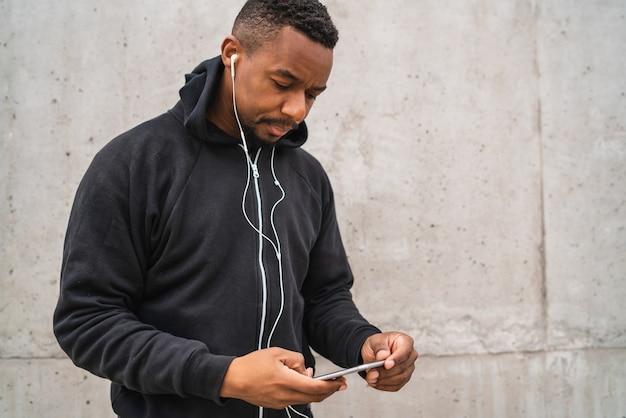 Retrato de un hombre atlético con su teléfono móvil en un descanso del entrenamiento contra un fondo gris. estilo de vida deportivo y saludable.