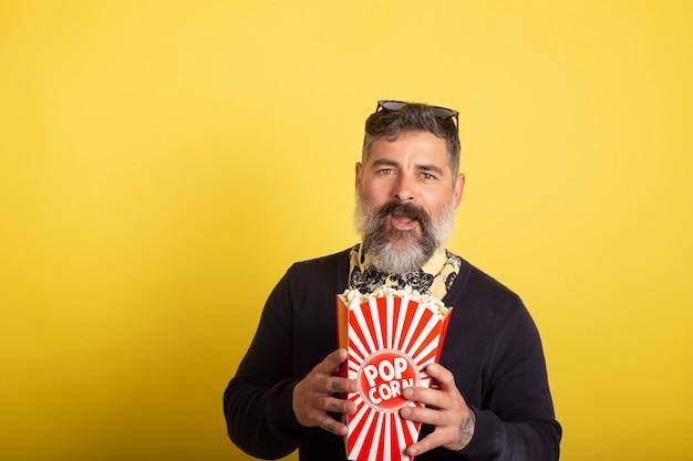 Retrato de hombre atractivo con barba blanca mirando sonriente hacia la cámara con una caja de palomitas de maíz sobre fondo amarillo.