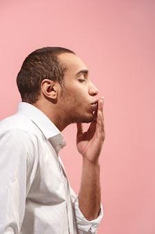 Retrato de hombre atractivo con beso aislado sobre espacio rosa