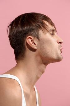 Retrato de hombre atractivo con beso aislado sobre pared rosa