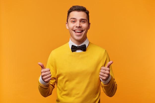 El retrato de un hombre atractivo con los pulgares hacia arriba parece tener un éxito, elegantemente vestido con un suéter amarillo sobre una camisa blanca con pajarita