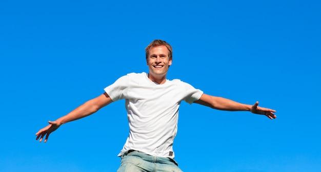 Retrato de un hombre atractivo saltando en el aire al aire libre
