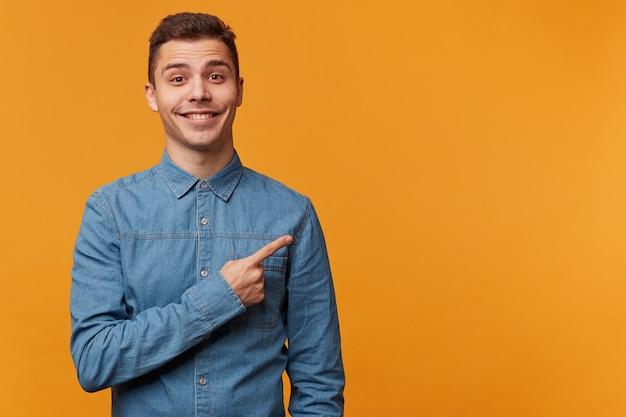 Retrato de un hombre atractivo satisfecho contento feliz en camisa de moda de mezclilla que muestra con su dedo índice la esquina superior derecha.
