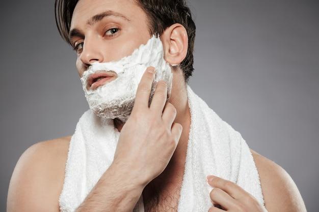Retrato de hombre atractivo con una toalla en el cuello poniendo espuma de afeitar en la cara, mientras que el cuidado de la piel por la mañana aislado sobre la pared gris