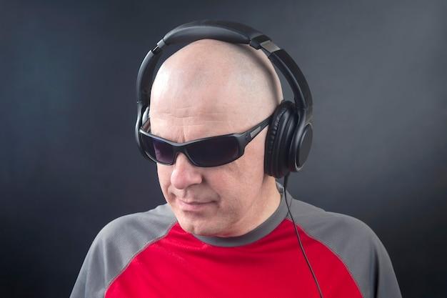 Retrato de un hombre con auriculares en la cabeza en relajación escuchando música