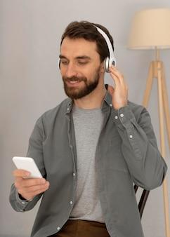 Retrato de hombre con auriculares escuchando música en el móvil