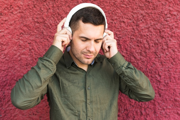 Retrato de hombre con auriculares escuchando música