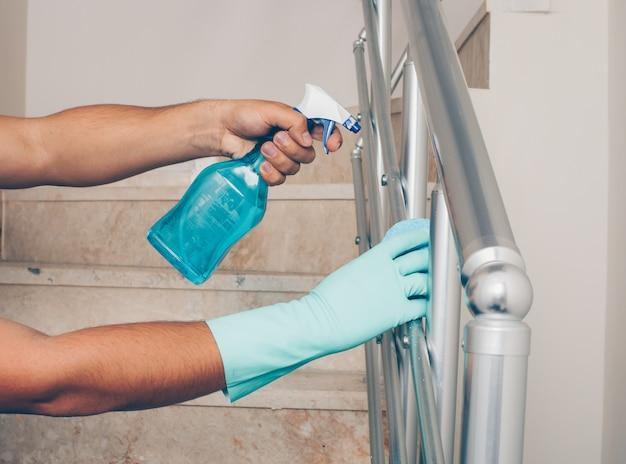 Retrato de un hombre de la barandilla de la escalera de limpieza en guantes