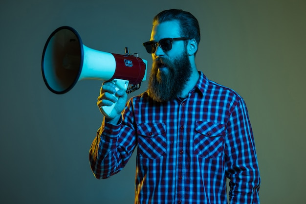 Retrato de hombre con barba hipster emocional con megáfono en el espacio en blanco en elegantes gafas de sol.