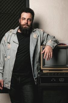 Retrato de hombre de barba junto a tv vintage