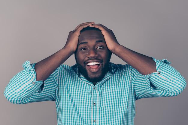 Retrato de hombre barbudo afroamericano emocionado feliz sosteniendo la cabeza y la boca abierta