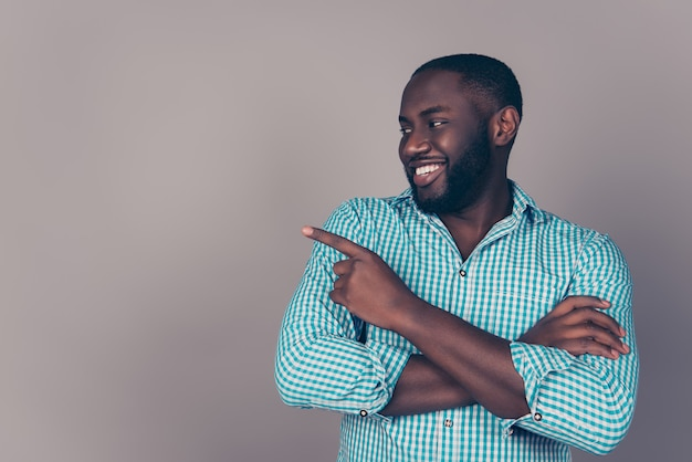Retrato de hombre barbudo afroamericano feliz apuntando algo en el espacio de la copia