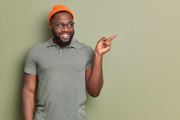 Retrato de hombre barbudo alegre señala a un lado en el espacio de la copia demuestra una buena promoción usa gafas, camiseta informal y sombrero aislado sobre una pared verde oscuro