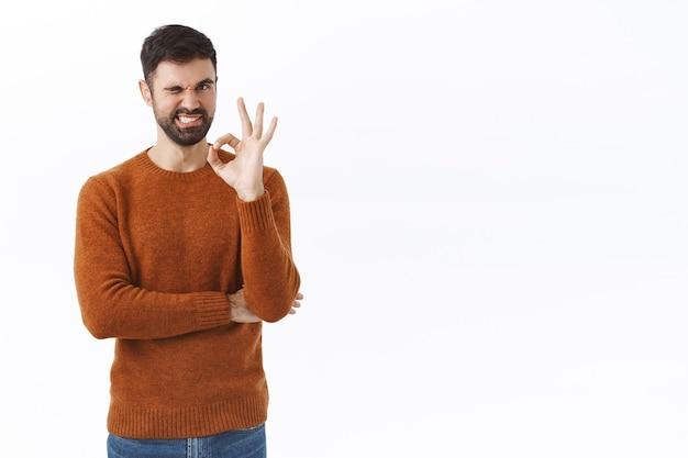 Retrato de hombre barbudo asertivo y guapo, asegura que la calidad es la mejor, muestra un signo de bien, guiña un ojo y sonríe asegurando, teniendo la confianza de recomendar algo, de pie complacido en la pared blanca