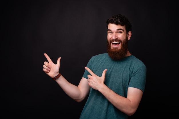 Retrato de hombre barbudo asombrado apuntando lejos en copyspace