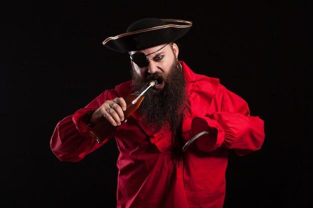 Retrato de hombre barbudo atractivo vestido como un pirata para halloween. pirata intentando abrir la botella con la boca.