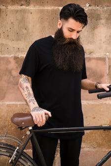 Retrato de un hombre barbudo con la bicicleta de pie delante de la pared