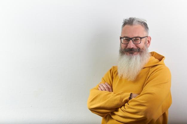 Retrato de hombre barbudo canoso maduro con capucha amarilla