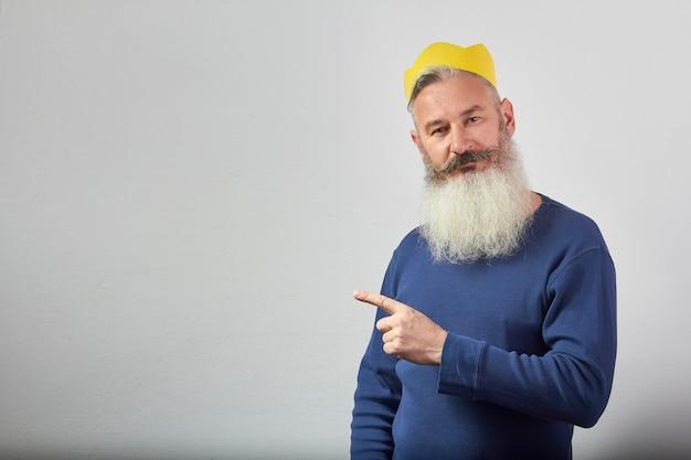 Retrato de hombre barbudo canoso maduro en corona de papel amarillo señala con el dedo
