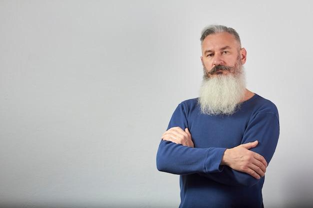 Retrato de hombre barbudo canoso maduro en sudadera azul