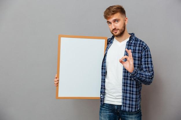 Retrato de un hombre barbudo casual sosteniendo tablero en blanco y mostrando gesto ok aislado en una pared gris