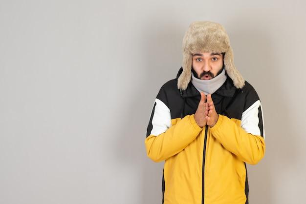 Retrato de hombre barbudo congelado en ropa de abrigo de pie y posando.