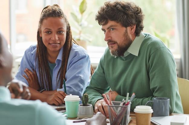 Retrato de hombre barbudo creativo intercambiando ideas mientras trabaja en un proyecto de equipo con un grupo multiétnico de personas
