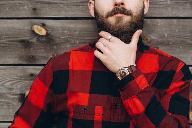 El retrato de un hombre barbudo elegante joven se vistió para arriba en pantalones vaqueros y un negro verdadero del trabajador por la camisa roja.