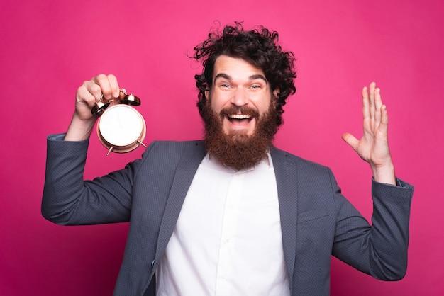 Retrato de hombre barbudo emocionado en traje sosteniendo despertador sobre fondo rosa