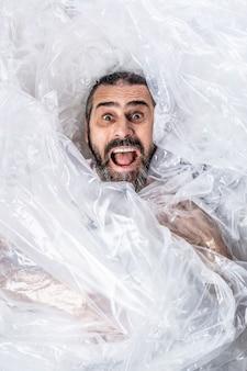 Retrato de un hombre barbudo envuelto en láminas de plástico.