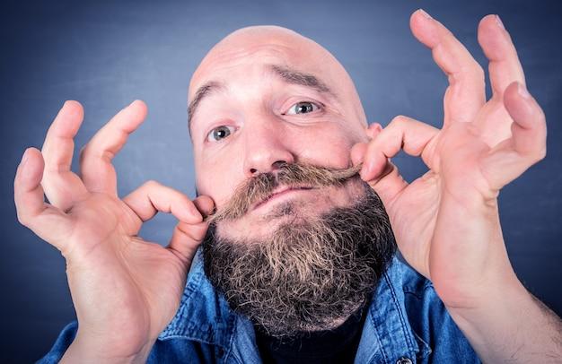 Retrato de hombre barbudo expresivo aislado en gris