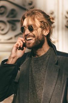 Retrato de un hombre barbudo feliz en gafas de sol