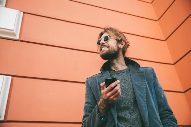 Retrato de un hombre barbudo feliz vestido con abrigo