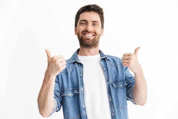 Retrato de un hombre barbudo guapo feliz con ropa casual que se encuentran aisladas, mostrando los pulgares para arriba