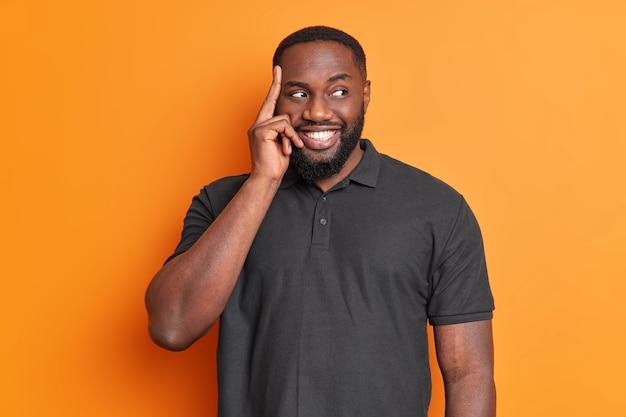 Retrato de hombre barbudo guapo pensativo mantiene el dedo en la sien sonríe agradablemente piensa en la decisión mira hacia otro lado vestido con camiseta negra casual aislada sobre pared naranja