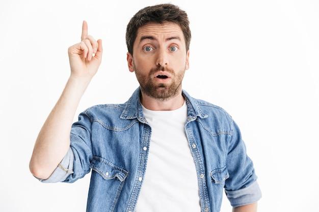 Retrato de un hombre barbudo guapo sorprendido con ropa casual que se encuentran aisladas, apuntando con el dedo hacia arriba