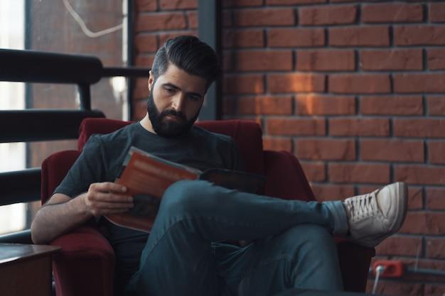 Retrato hombre barbudo guapo vistiendo ropa casual, sentado en una silla roja loft moderno