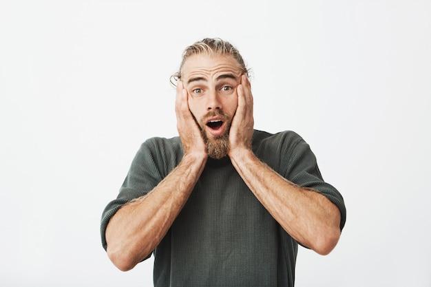 Retrato de hombre barbudo hermoso con buen peinado cogidos de la mano en la cabeza en excitemen