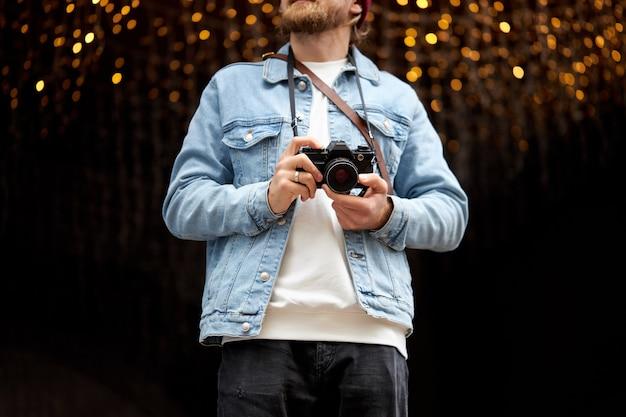 Retrato de hombre barbudo hipster recortada con cámara de película retro, haciendo fotos mientras camina en la ciudad. fondo urbano, guirnaldas de luces. copia espacio