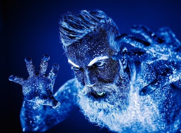 Retrato de un hombre barbudo, el hombre está pintado en polvo ultravioleta.