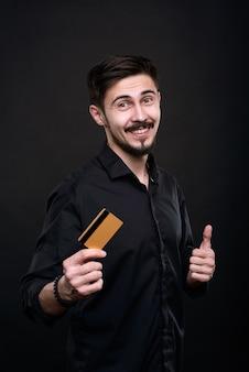 Retrato de hombre barbudo joven emocionado en camisa negra que muestra el pulgar hacia arriba mientras da a la tarjeta dorada altas calificaciones