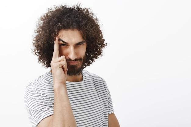 Retrato de hombre barbudo juguetón sospechoso con pelo rizado, levantando la ceja con el dedo índice