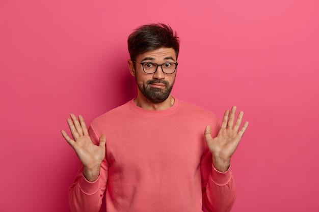 Retrato de hombre barbudo levanta las palmas de las manos, muestra que beig no está involucrado o es culpable
